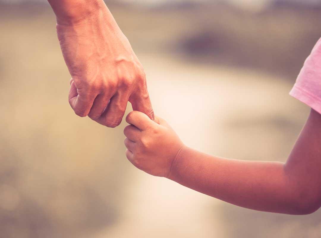 volwassene neemt hand van kind